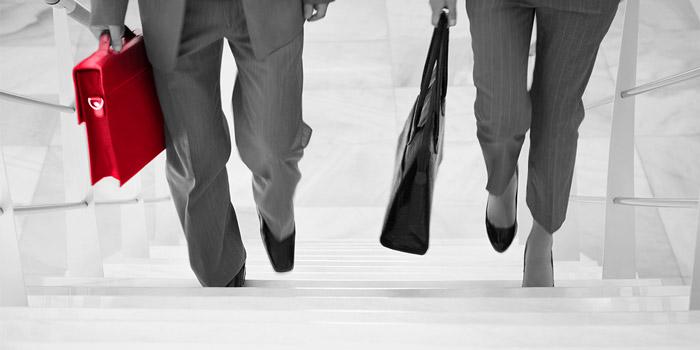 Business people walking up stairs | Atradius